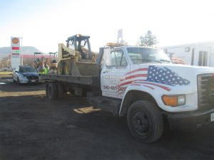 equipment hauling truck with american flag on the front