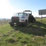 Shenandoah towing and recovery services truck on a grassy field with a blue sunny sky