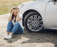woman sitting roadside next to broken down car waiting for towing company